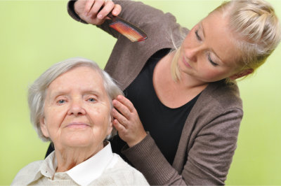 Homecare staff combing hair of elder woman